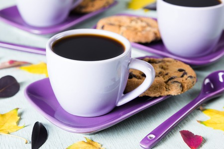 Colourful fall leaves and Purple coffee cup on light blue background