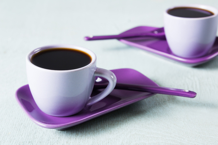 Purple coffee cup with saucer and biscuit on light blue background