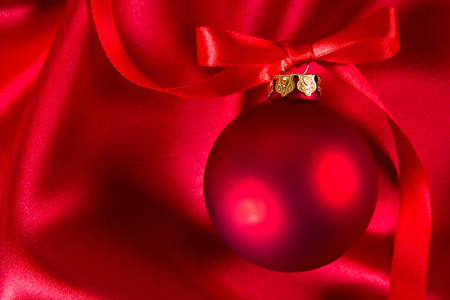 textil: Red christmas ball with red ribbon on a red silk cloth Stock Photo