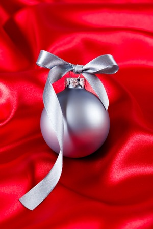 Silver christmas ball with red ribbon on a red silk cloth