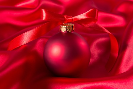 Red christmas ball with red ribbon on a red silk cloth Stock Photo