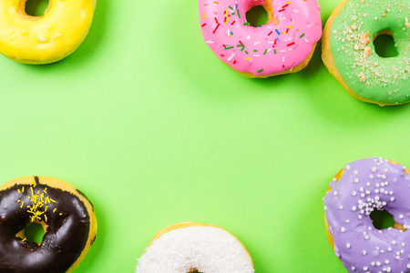 Colorful round donuts on green background. Flat lay, top view.