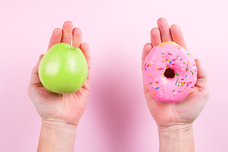 Hands choosing between apple and donut as concept of healty lifestyle Stock Photo