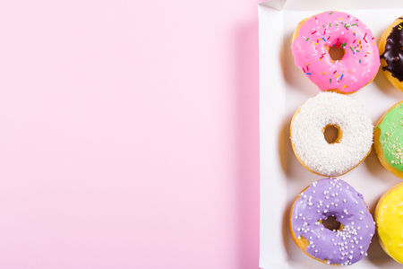 Six colorful round donuts in the box. Flat lay, top view.