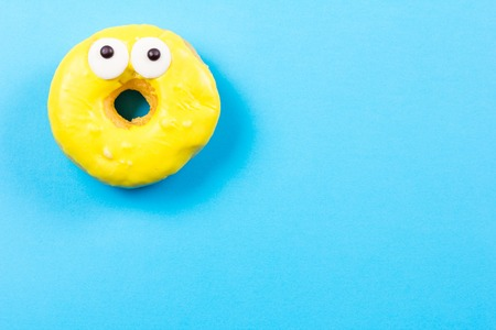 Yellow round donut with eyes on blue background. Flat lay, top view.