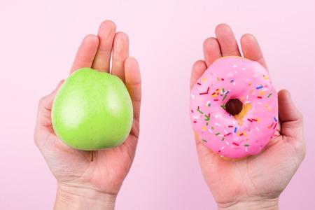 Handen kiezen tussen appel en donut als concept van gezonde levensstijl