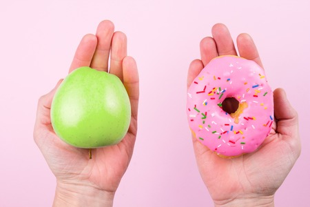 Hands choosing between apple and donut as concept of healty lifestyle Imagens