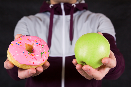 choise: Man offering apple and donut as concept of healty lifestyle Stock Photo