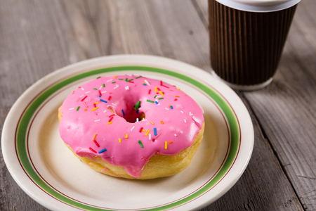 fresh donut and take away coffee, wooden background with copy space