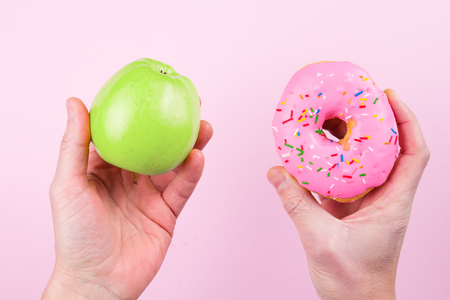 choise: Hands choosing between apple and donut as concept of healty lifestyle Stock Photo