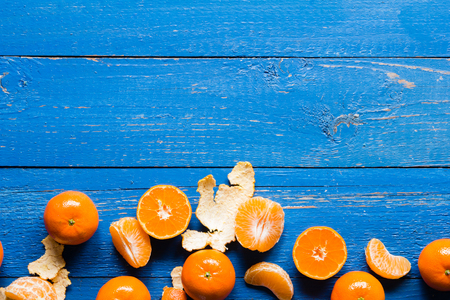 cutted: Whole, cutted and pilled mandarins on a blue painted wooden background