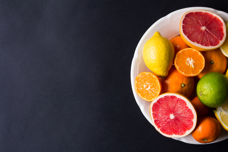 various types of citrus fruit on a dark background