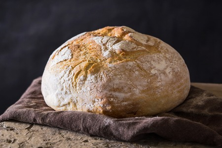 Homemade bread loaf on old table. Dark background