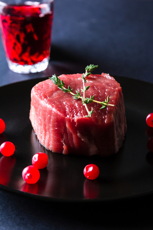 Raw meat herbs and berries on black plate and dark background. Minimalistic still life