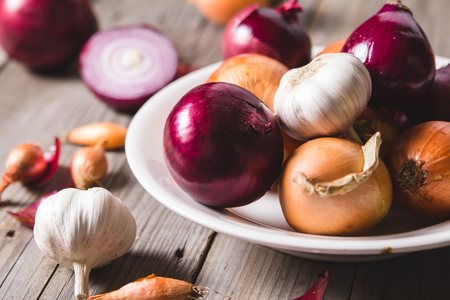 Several kinds of different onion bulbs at a white plate, standing on an old wooden table. Above view still life Stock Photo