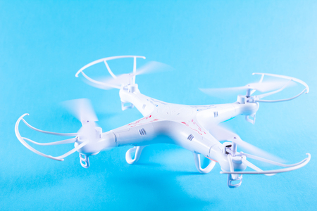 spyware: Photo of white quadrocopter on bright blue background