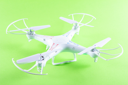Photo of white quadrocopter on bright green background. Above view Stock Photo