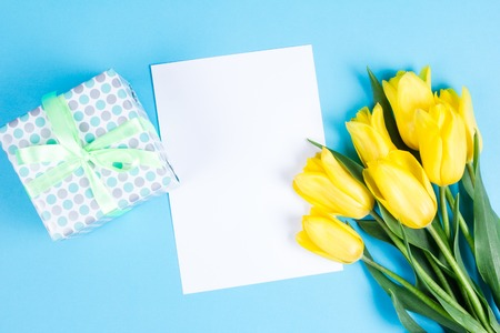 Bouquet of beautiful fresh yellow tulips on Blue background. View from above photo. Space for text Stock Photo