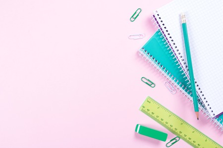 School stationery on pink background with copyspace