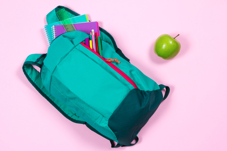 Backpack with school stationery and apple on pink background