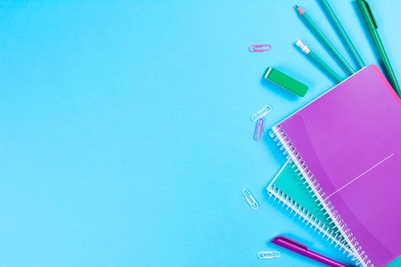 School stationery on blue background with copyspace. Flat lay