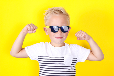 Cute blond boy wearing sunglasses on yellow background showing muscles
