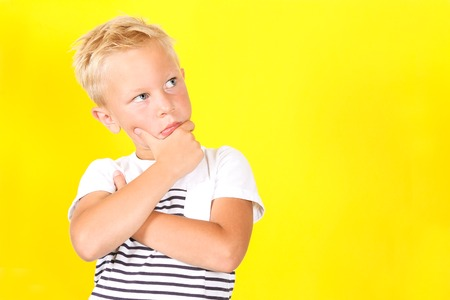 Cute blond boy portrait dreaming of something on yellow background Banco de Imagens