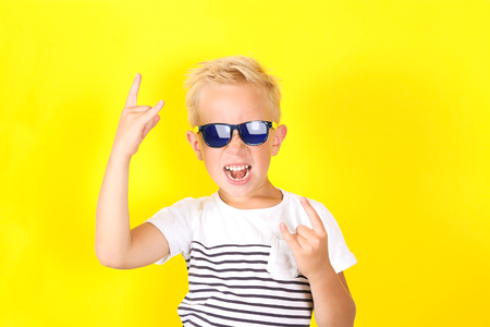 Cute blond boy wearing sunglasses on yellow background showing Horns gesture