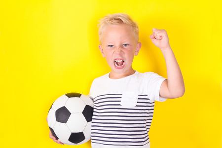 Cute blond boy portrait with ball on yellow background locking football game