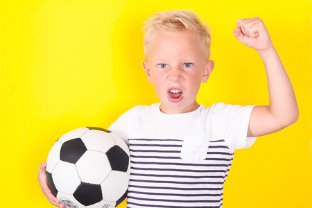 Cute blond boy portrait with ball on yellow background