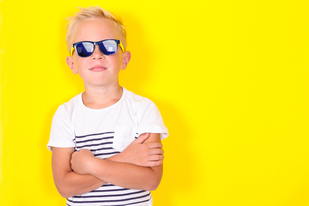Cute cool blond boy wearing sunglasses looking at camera