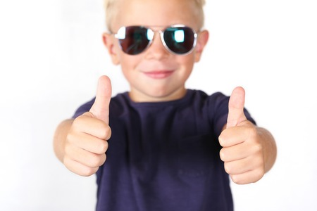 Cute blond boy wearing sunglasses on white background showing Thumbs Up Banco de Imagens