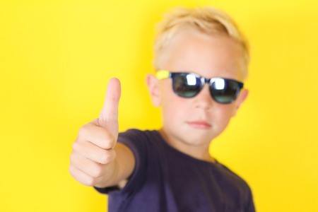 Cute blond boy wearing sunglasses on yellow background showing Thumbs Up Banco de Imagens