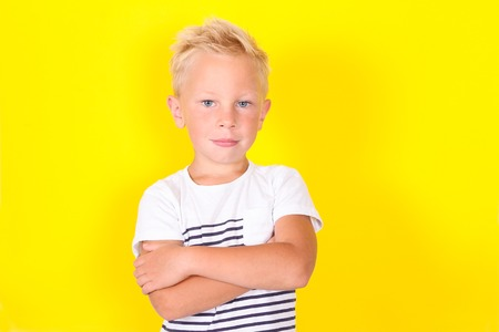 Cute blond boy portrait on yellow background