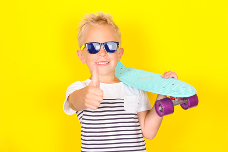 Bright portpait on yellow background of cute cool blond boy wearing sunglasses with skateboard in his arms Banco de Imagens