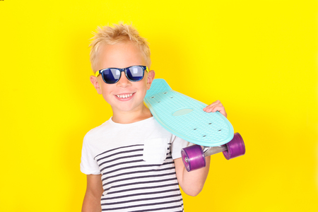 Bright portpait on yellow background of cute cool blond boy wearing sunglasses with skateboard in his arms 写真素材