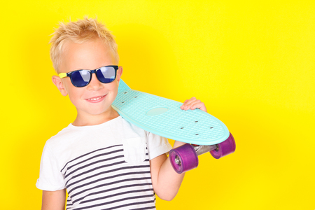 Cute cool blond boy wearing sunglasses with skateboard in his arms Banco de Imagens