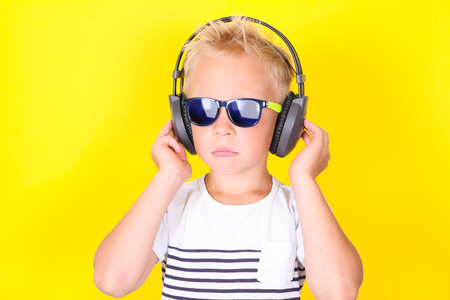 Bright portpait on yellow background of cute cool blond boy wearing sunglasses and earphones Banco de Imagens