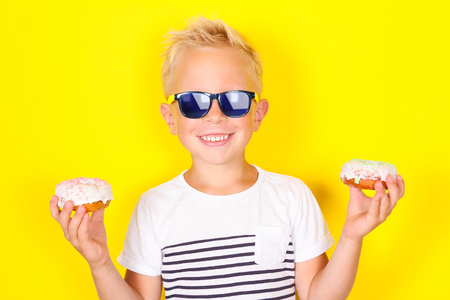 Bright portpait on yellow background of cute cool blond boy wearing sunglasses and enjoing donut Banco de Imagens