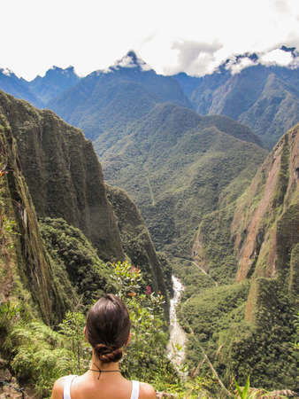 Woman looking at the river Urubamba on a hiking path in Machu Picchu Stock Photo