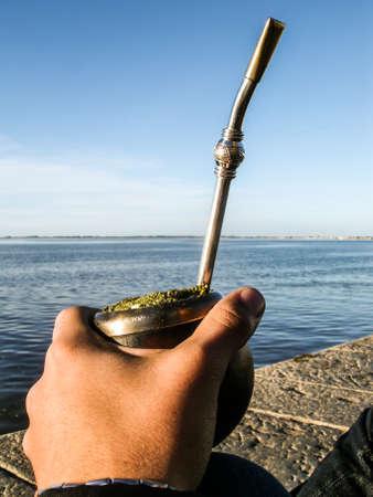 yerba mate: Mano masculina que sostiene un compañero - bebida tradicional de Suramérica