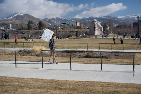 ut: Salt Lake City, UT, USA - January 31, 2015: A protester holds a sign in front of the Utah State Capitol building for the Clean Air, No Excuses rally. Editorial