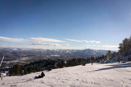 wasatch: Huntsville, UT, USA - November 26, 2014. Skiers and snowboarders enjoy the sun during opening day at Snowbasin ski resort.