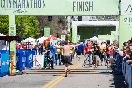 April 18, 2015: Salt Lake City, Utah. USA - A shirtless runner crosses the finish line of the Salt Lake City Marathon with his arms raised and a small crowd in the background