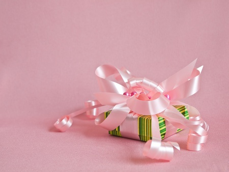 Green gift box with pink ribbon and bow on the pink background. photo