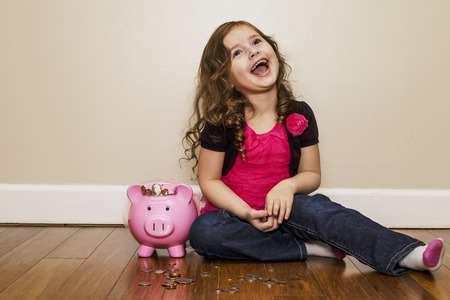 passive earnings: little girl laughing while counting her money Stock Photo