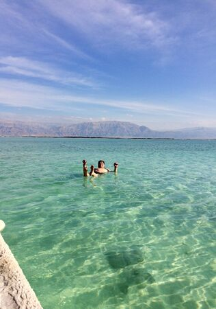 A man lies on the surface of the water at the Dead Sea in Jerusalem ? person standing next to a body of waterundefined