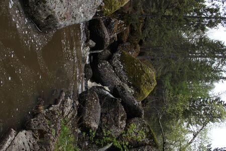 A mountain river waterfall flows through a river bed through huge boulders with moss Stock fotó
