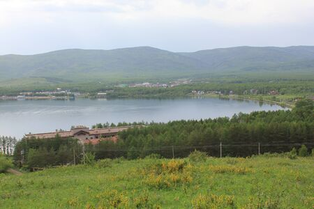 Panoramic view. A lagoon with a clean mountain lake in the midst of majestic mountains in a haze of fog. Green grass. Apartments around the lake Zdjęcie Seryjne