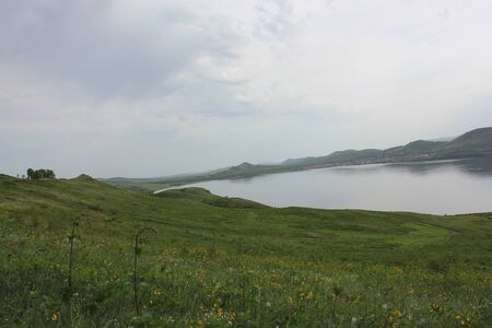 Panoramic view. A lagoon with a clean mountain lake in the midst of majestic mountains in a haze of fog. Green grass. Apartments around the lake Фото со стока